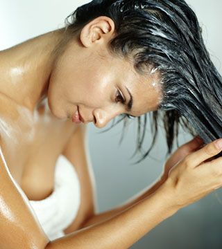 Young woman rubbing conditioner through hair
